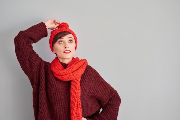 여자가 그녀의 겨울 모자 끝을 들고