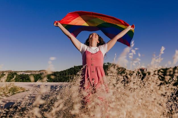 夕暮れ時のゲイ虹色の旗を保持している女性。同性カップルのための幸福、自由、愛の概念。アウトドアライフスタイル