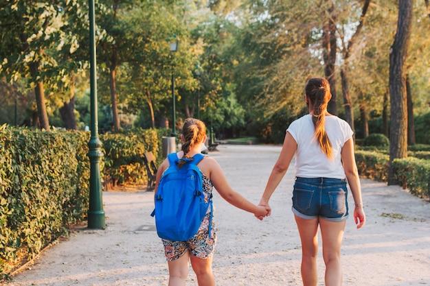 Женщина держит руку своей дочери. поступление в школу.