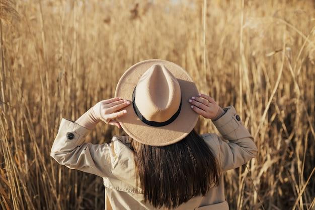 帽子に手をかざし、乾いた葦に立っている女性
