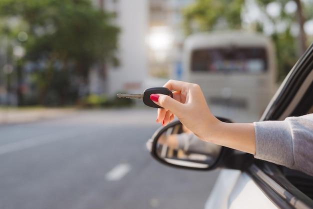 열린 쪽 창문을 통해 차의 시동 키를 손에 들고 있는 여성