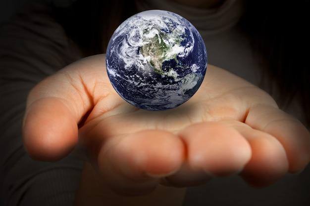 手に惑星地球を保持している女性。 nasaから提供されたこの画像の要素