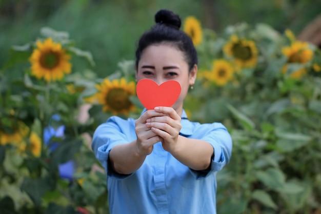 Женщина держит символ любви перед ее лицом