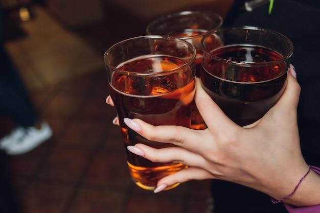 Женщина, держащая три бокала пивного бармена.