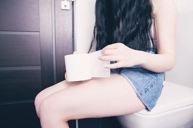 Женщина держит в руках туалетную бумагу