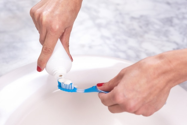 Woman holding a tooth brush putting toothpaste on it.