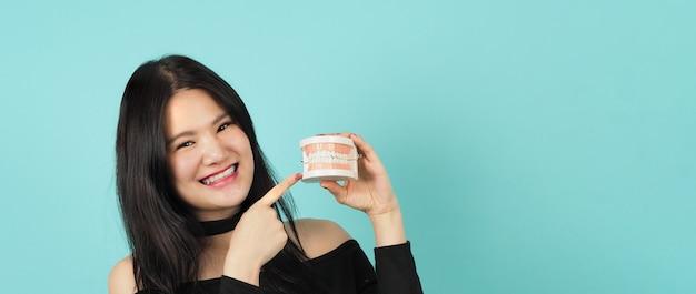 歯ブラシと歯のモデルまたは歯科矯正モデルを保持している女性。口腔ヘルスケアの概念。