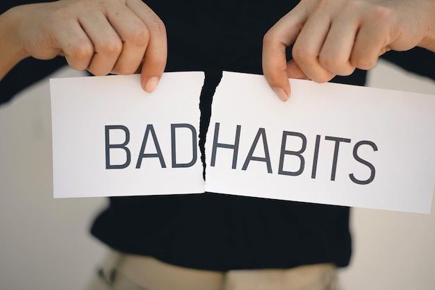 Woman holding a torn paper hands with the words bad habits , self development concept