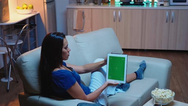 Женщина, держащая тачпад с зеленым экраном, сидя на софе в гостиной. домохозяйка, глядя на шаблон цветного ключа, изолировала дисплей смарт-ноутбука, используя интернет технологии, сидя на диване.