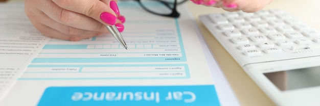 Woman holding toy car in her hands and filling out insurance form closeup