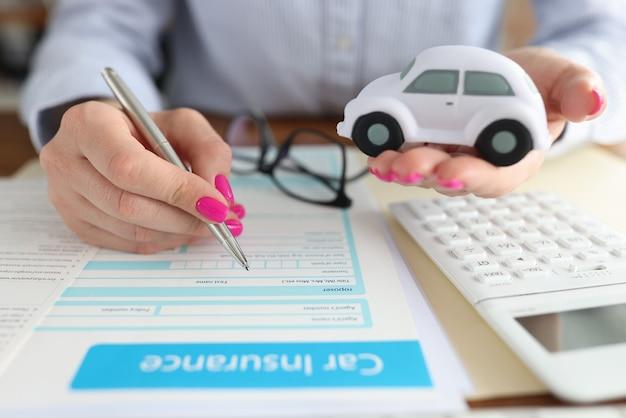 여자가 그녀의 손에 장난감 자동차를 들고 보험 양식 근접 촬영을 작성