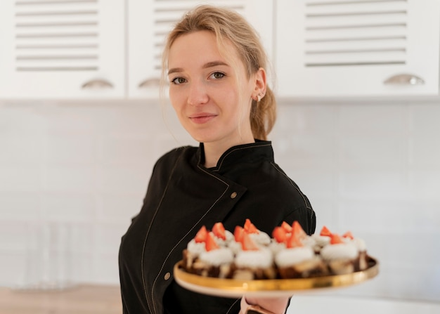 Woman holding tray with dessert