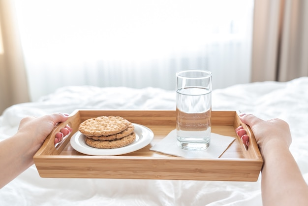 Woman holding tray with diet breakfast of crackers and water on a bed