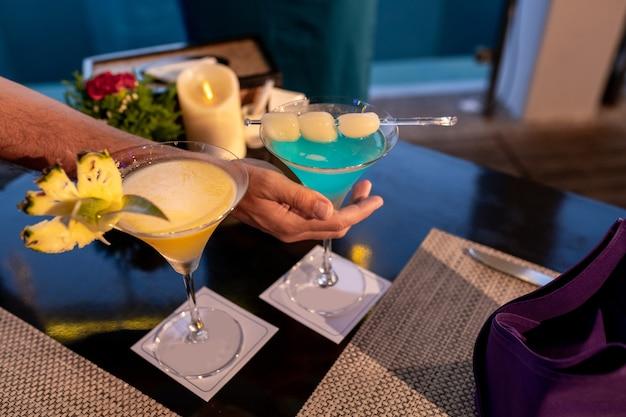 Женщина, держащая тропические коктейльные напитки