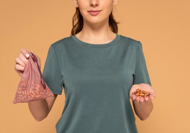 豆とタートルバッグを保持している女性