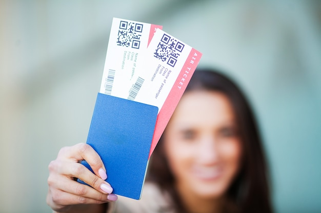 Woman holding two air ticket in abroad passport near airport