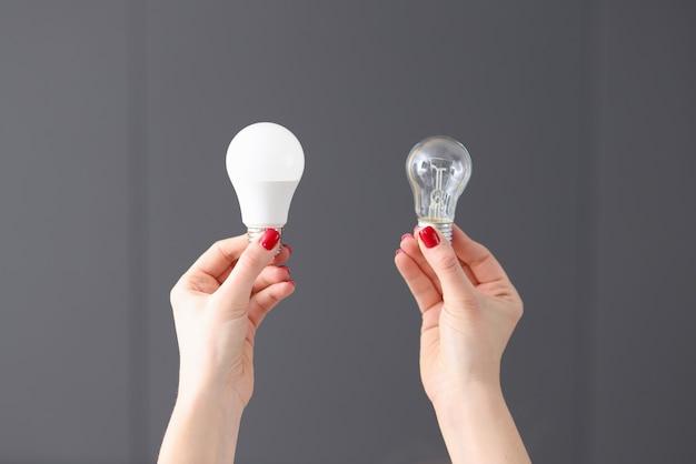 여자는 그녀의 손에 근접 촬영에 두 개의 다른 전구를 들고. 사업 개발 개념에 대한 아이디어