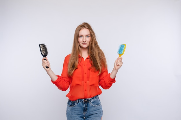 Woman holding two hairbrush posing with one half shaggy and combed hair medium shot