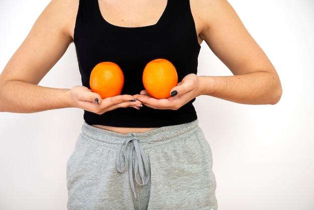 Женщина, держащая два апельсина перед ее грудью, концепция осведомленности рака молочной железы