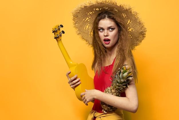 우쿨렐레 밀짚 모자 라이프 스타일 이국적인 노란색 배경을 들고 여자