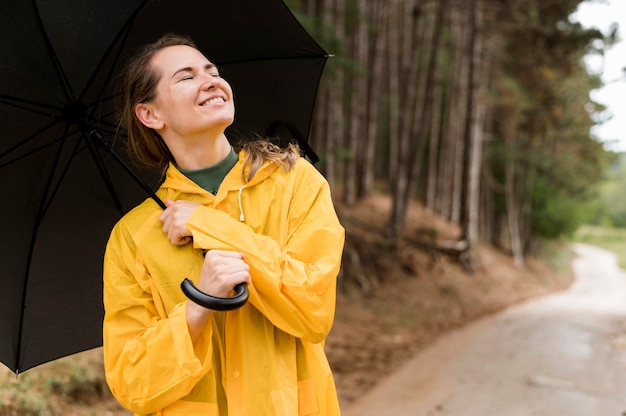 Woman holding an umbrella above her head with copy space