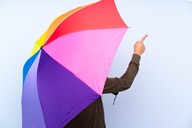 Woman holding an umbrella over isolated wall