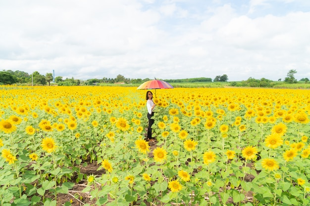 Woman holding an umbrella in a sunflower field.
