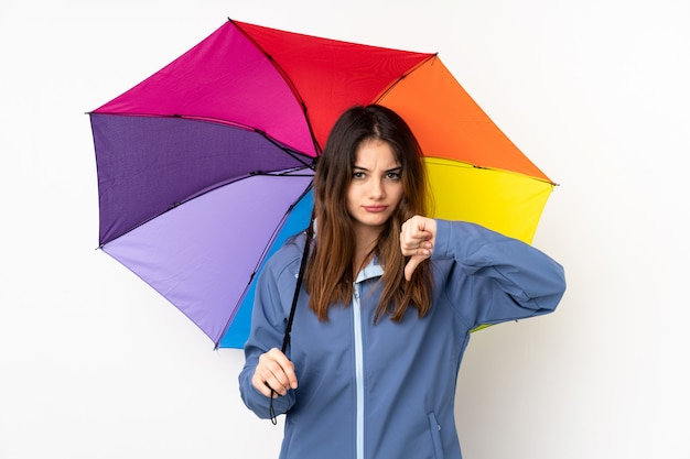 Woman holding an umbrella on white wall showing thumb down sign