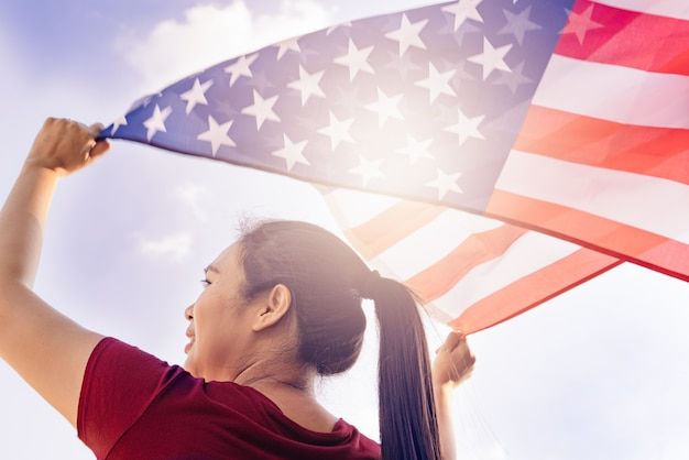 Woman holding united states of america flag on sunny sky. usa memorial day and independence day concept.