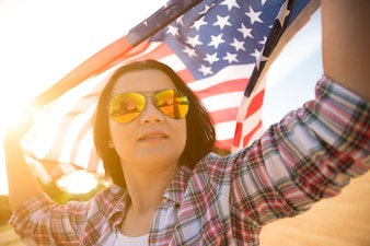Woman holding United States of America flag on beach.