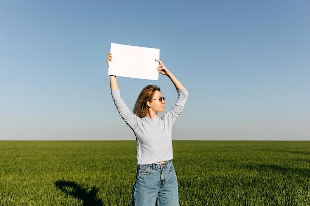 青い空に白紙を保持している女性。