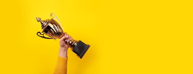 Женщина держит золотой трофейный кубок как победитель конкурса, панорамное изображение