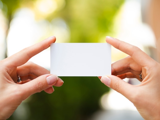 Woman holding up a business card mock-up