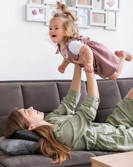 Woman holding up little girl