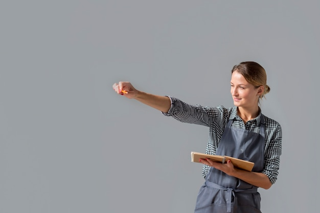 Woman holding up pencil with copy space