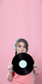 Woman holding up vinyl record while wearing headphones