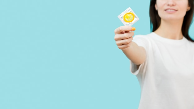 Woman holding up a yellow condom with copy space