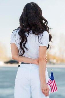 여자가 뒤에서 미국 국기를 들고