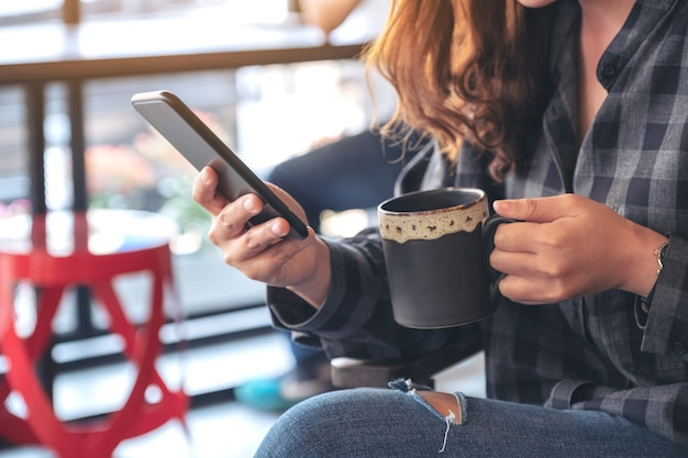 Woman holding , using and looking at smart phone while drinking coffee in cafe