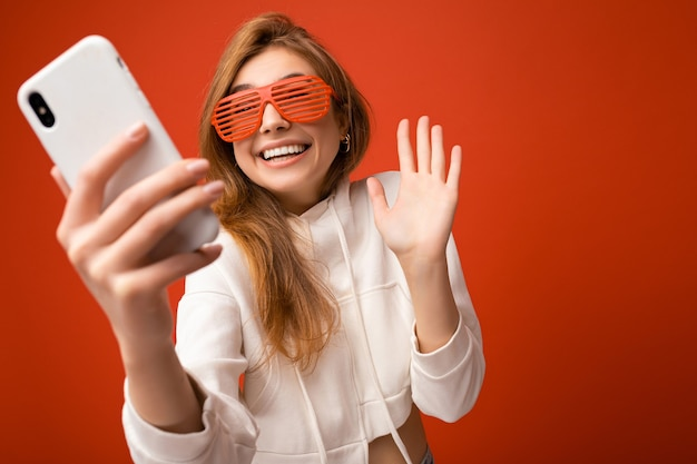 Woman holding and using mobile phone taking selfie wearing stylish clothes isolated over wall background.