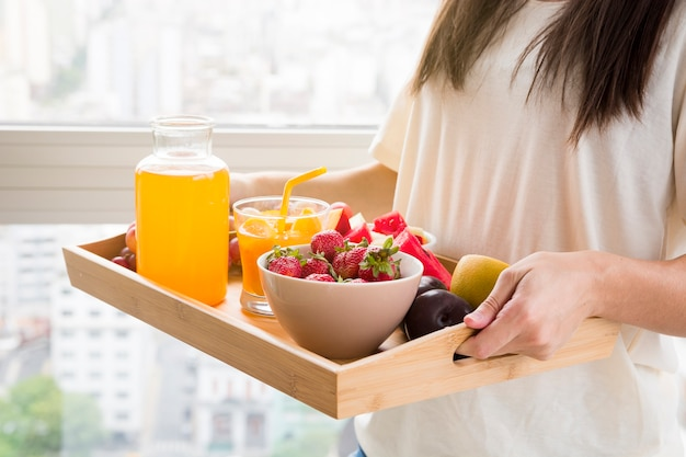 Woman holding various fruits and juice bottle on wooden tray