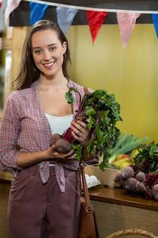 Женщина держит овощи в продуктовом магазине
