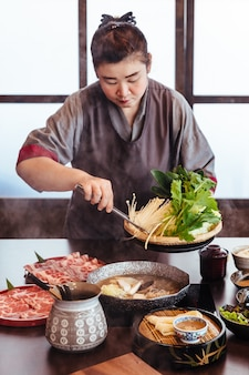 A woman holding vegetables into hot pot by tongs with wagyu a5 beef and sliced kurobuta in shabu.