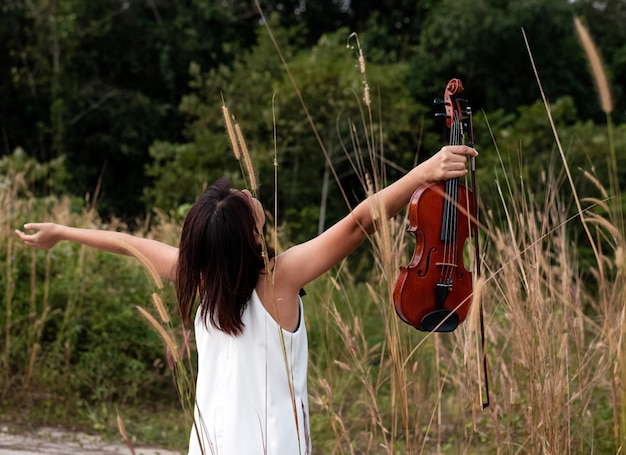 Woman holding violin in hand and raise up in the air