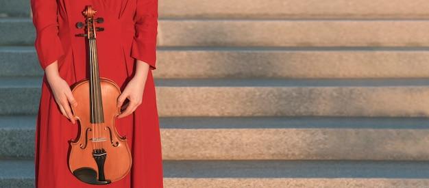 Женщина держит скрипку рядом с шагами