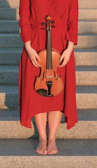 Женщина держит скрипку во время позирует на шагах