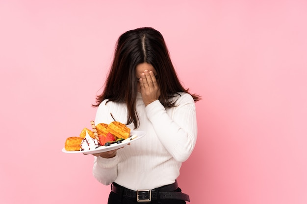 Woman holding waffles over isolated wall