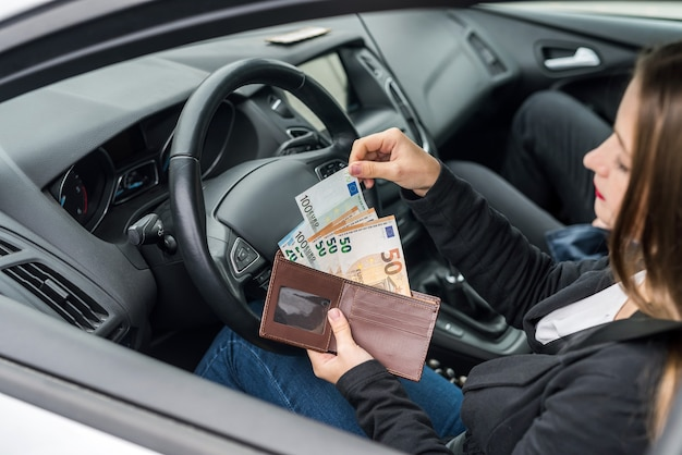 Woman holding wallet with euro sitting in car