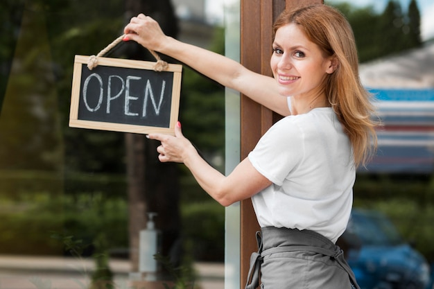 Woman holding we are open sign