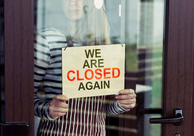 Woman holding we're closed sign